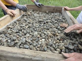Steine als Hitze-Puffer zwischen den Holzpaletten und der Schamottplatte